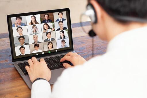 ヘッドフォンとノートパソコンを使用して、Web会議(Wherebyなど)で複数の相談者に応じる男性行政書士。